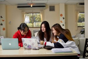 Students study in the common area of a boarding house
